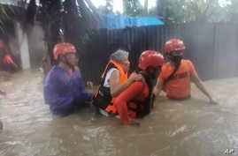 In this photo provided by the Philippine Coast Guard, rescuers evacuate residents to safer ground as floods caused by Tropical…