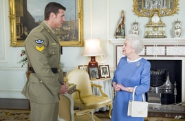 Britain's Queen Elizabeth II greets Corp. Ben Robert-Smith, from Australia, who was recently awarded the Victoria Cross, during…
