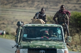 FILE - In this Saturday, May 8, 2021 file photo, Ethiopian government soldiers ride in the back of a truck on a road near Agula…