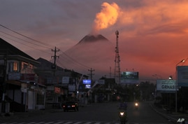Motorists ride past as Mount Merapi looms in the background, in Sleman, Friday, June 25, 2021. Indonesia's most volatile…