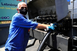 A worker pumps gasoline from a fuel truck to supply a gas station in Beirut, Lebanon, Friday, June 25, 2021. Lebanon's…