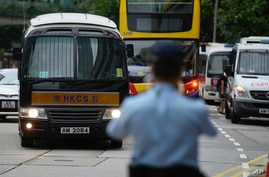 A prison van, left, which a police officer says is carrying Tong Ying-kit arrives at a court in Hong Kong Wednesday, June 23,…