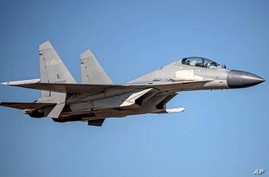 In this undated file photo released by the Taiwan Ministry of Defense, a Chinese PLA J-16 fighter jet flies in an undisclosed…