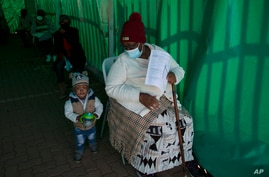 An elderly woman with a young child queues to receive her Pfizer COVID-19 vaccine, at a clinic at Orange Farm, near…