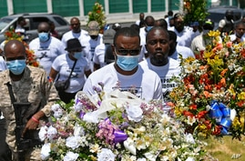 Pierre Gary Bernadotte, a member of the slain president's PHTK political party, carries flowers to a spot outside the…