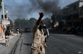 Police clear burning tire road blocks set by protesters upset with growing violence in the Lalue neighborhood of Port-au-Prince…