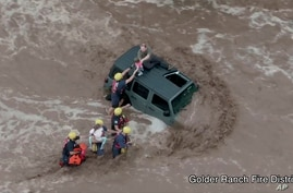 This drone image provided by the Golder Ranch Fire District shows firefighters safely rescue a man and his two daughters from…
