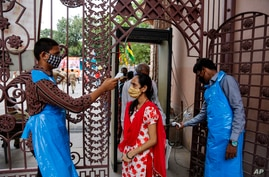 An Indian man checks the temperature of a devotee on the eve of the annual Rath Yatra, or Chariot procession of Lord Jagannath,…