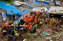 Rescuers look for survivors after a wall collapsed on several slum houses heavy monsoon rains in the Mahul area of Mumbai,…