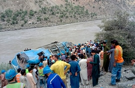 Local residents and rescue workers gather at the site of bus accident, in Kohistan Kohistan district of Pakistan's Khyber…