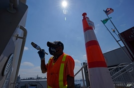 John Ford, a worker with the Port of Seattle, paints near a railing at the Bell Street Cruise Terminal at Pier 66, Wednesday,…