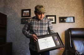 In this Monday, Dec. 16, 2019, photo, Zia Ghafoori displays the Purple Heart at his home in Charlotte, N.C., that he received…