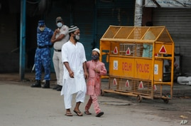 Indian para-military force soldiers stand guard as Indian Muslims walk past closed shops on Eid al Adha following Covid…