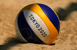 A volleyball rests in the sand during during women's beach volleyball practice at the 2020 Summer Olympics, Monday, July 19,…