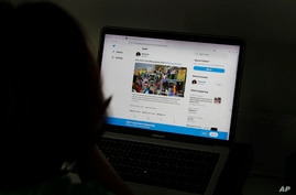 A woman looks at the Twitter page of pop star Rihanna in New Delhi, India, Thursday, July 15, 2021. It began in February with a…