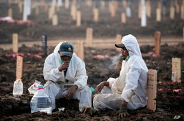 Workers take a break during a busy day at Rorotan Cemetery, which is reserved for those who died of COVID-19, in Jakarta,…