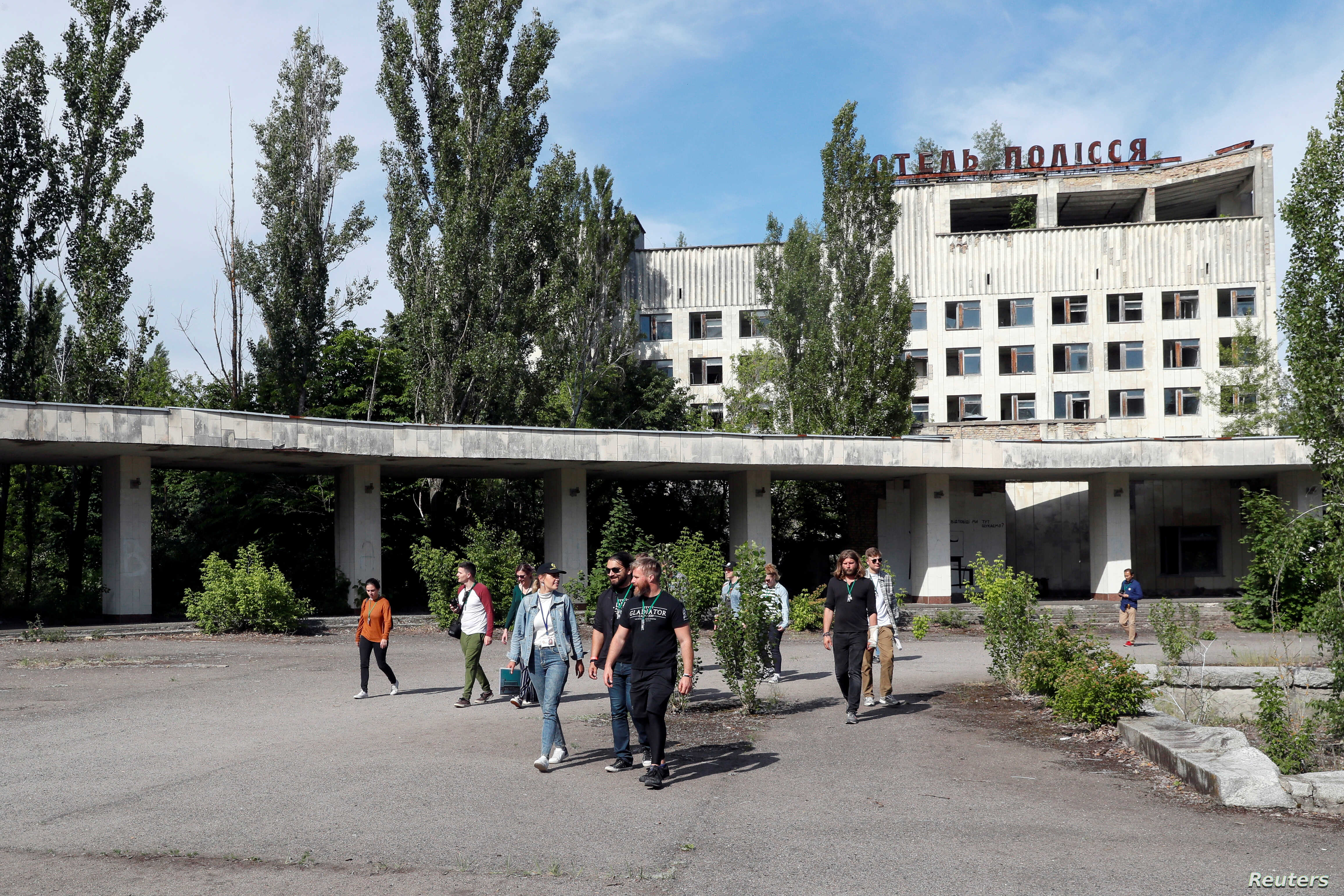 Visitors walk in the abandoned city of Pripyat, near the Chernobyl nuclear power plant