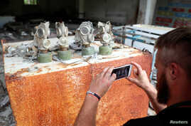A visitor takes a picture of gas masks at a former base of the Soviet army, near the Chernobyl Nuclear Power Plant.