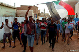 FILE PHOTO: Sudanese protesters chant slogans and wave their national flag as they demonstrate against the ruling military council, in Khartoum
