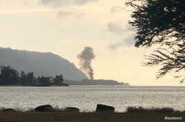 A plume of smoke rises after an airplane crash, seen from Kaiaka Bay Beach Park, in Haleiwa, Hawaii, June 21, 2019.