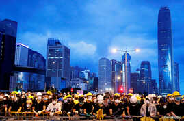 Anti-extradition bill protesters stand behind a barricade during a demonstration near a flag-raising ceremony for the anniversary of Hong Kong handover to China  in Hong Kong, July 1, 2019.