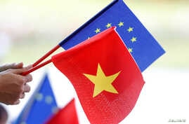 European Union and Vietnamese flags are seen at the signing ceremony of the of EU-Vietnam Free Trade Agreement, June 30, 2019, in Hanoi.