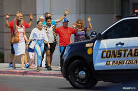 Shoppers exit with their hands up after a mass shooting at a Walmart in El Paso