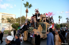 FILE PHOTO: Supporters of Libyan National Army (LNA) commanded by Khalifa Haftar, celebrate on top of a Turkish military armored vehicle, which LNA said they confiscated during Tripoli clashes, in Benghazi
