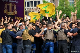 Lebanese army try to block supporters of the Lebanese Shi'ite groups Hezbollah and Amal as they gesture and chant slogans against anti-government demonstrators, in Beirut