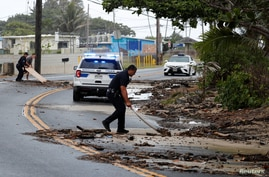 Police officers and a bystander use plywood boards to push debris off the road in Kaaawa