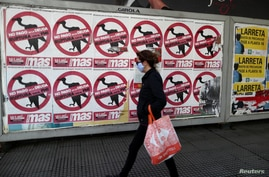 "FILE PHOTO: A pedestrian wearing a protective face mask walks past posters on the street that read ""No to the payment of the debt. Break with the IMF"", in Buenos Aires"