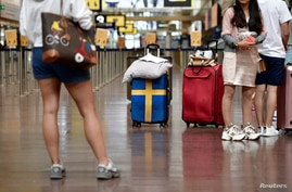 Passengers prepare to check in at Arlanda airport for the first chartered TUI flight  to Rhodes in Greece since the outbreak of the coronavirus disease (COVID-19), in Stockholm