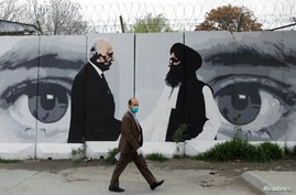 FILE PHOTO: An Afghan man wearing a protective face mask walks past a wall painted with photo of Zalmay Khalilzad, U.S. envoy for peace in Afghanistan, and Mullah Abdul Ghani Baradar, the leader of the Taliban delegation, in Kabul