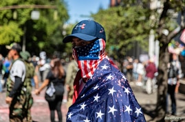A man dressed in an American flag joins protesters in Portland