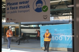 People are seen on a train platform below a sign encouraging the use of protective face masks in the city centre in Sydney