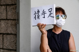 """A woman holds up a paper pad that reads """"support sibling"""" while waiting outside the court to bid farewell to a prison van transporting Tong Ying-kit in Hong Kong"""