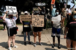 People protest after a Black man identified as Jacob Blake was shot several times by police in Kenosha