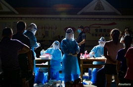 Medical workers attend to people lining up for nucleic acid testing at a residential compound in Ruili