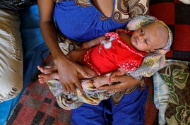 Ethiopian refugee Salam Gberedanos holds her 22 days old daughter Abeyam, at the Village 8 refugees transit camp, which houses Ethiopian refugees fleeing the fighting in the Tigray region, near the Sudan-Ethiopia border
