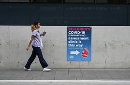 A person walks past a sign for a coronavirus disease (COVID-19) assessment clinic in Sydney in Sydney
