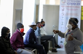 FILE PHOTO: A medical worker talks to volunteers as they wait to receive an injection during the country's first human clinical trial for a potential vaccine against the novel coronavirus, in Soweto