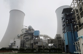 FILE PHOTO: Water vapour rises from a cooling tower of a China Energy ultra-low emission coal-fired power plant during a media tour, in Sanhe