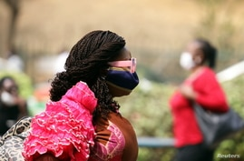 A woman wears a protective face mask following the closure of Wuse market for failing to adhere to COVID-19 prevention protocols in Abuja