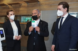 """FILE - Israeli Prime Minister Benjamin Netanyahu, center, holds up a document, that is part of the """"Green Pass"""" system, which grants certain privileges to citizens who have had both doses of the vaccine against the coronavirus disease (COVID-19) or have recovered from COVID-19, in Modiin, Israel March 4, 2021."""