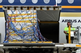 The first Australian shipment of Pfizer coronavirus disease (COVID-19) vaccines is unloaded from a Singapore Airlines plane at Sydney International Airport