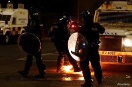 A police officer reacts next to fire during a protest in the Loyalist Tigers Bay Area of Belfast, Northern Ireland April 9, 2021.