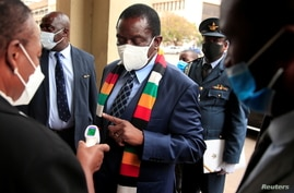 FILE PHOTO: Zimbabwe's President Mnangagwa has his temperature taken as he arrives at the parliament in Harare