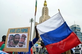 Malians hold an image with coup leader leader Goita during a pro-FAMA  demonstration in Bamako