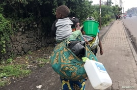 A Congolese woman carries her child and belongings as they evacuate from recurrent earth tremors as aftershocks following the eruption of Mount Nyiragongo volcano near Goma