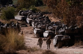 Israeli soldiers walk next to tanks near the border between Israel and the Gaza Strip, on its Israeli side